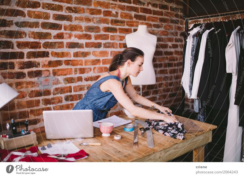 Young female fashion designer working in her studio Human being Youth (Young adults) Young woman Lifestyle Feminine Business Work and employment Office Technology Creativity Profession Factory Home Desk Workplace Notebook