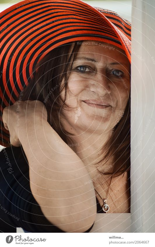 smiling mature woman with red hat Feminine Woman Adults Human being Necklace Hat Brunette Smiling Direct portrait Looking into the camera Attractive Striped