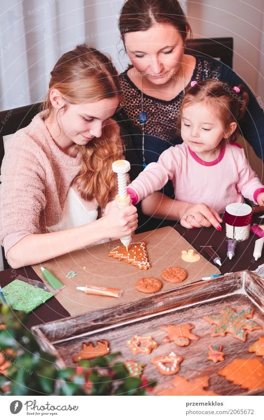 Family decorating baked Christmas gingerbread cookies with frosting Decoration Table Kitchen Feasts & Celebrations Child Human being Woman Adults