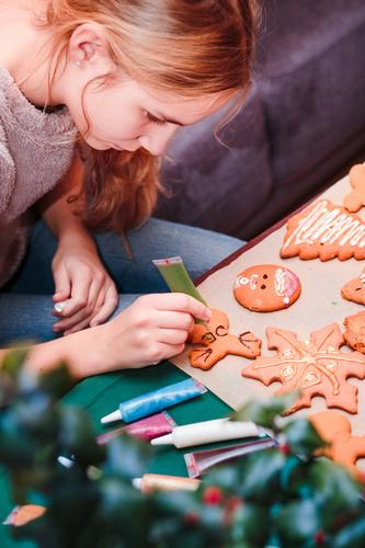 Girl decorating Christmas gingerbread cookies with chocolate Food Lifestyle Decoration Table Feasts & Celebrations Christmas & Advent Human being 13 - 18 years
