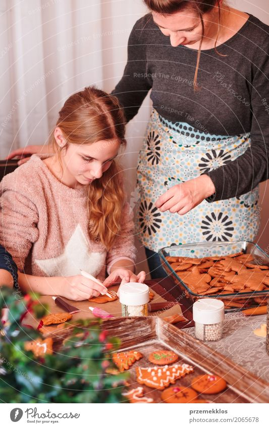 Girl decorating Christmas gingerbread cookies with frosting Human being Child Woman Christmas & Advent Adults Lifestyle Decoration Infancy Table Kitchen