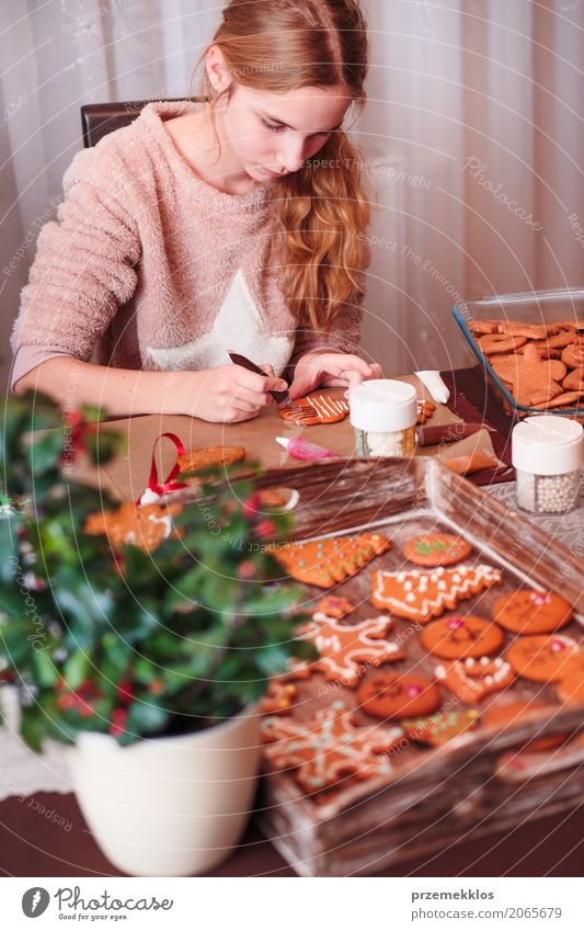 Girl decorating Christmas gingerbread cookies with frosting Human being Child Lifestyle Feasts & Celebrations Decoration Infancy Table Kitchen 8 - 13 years