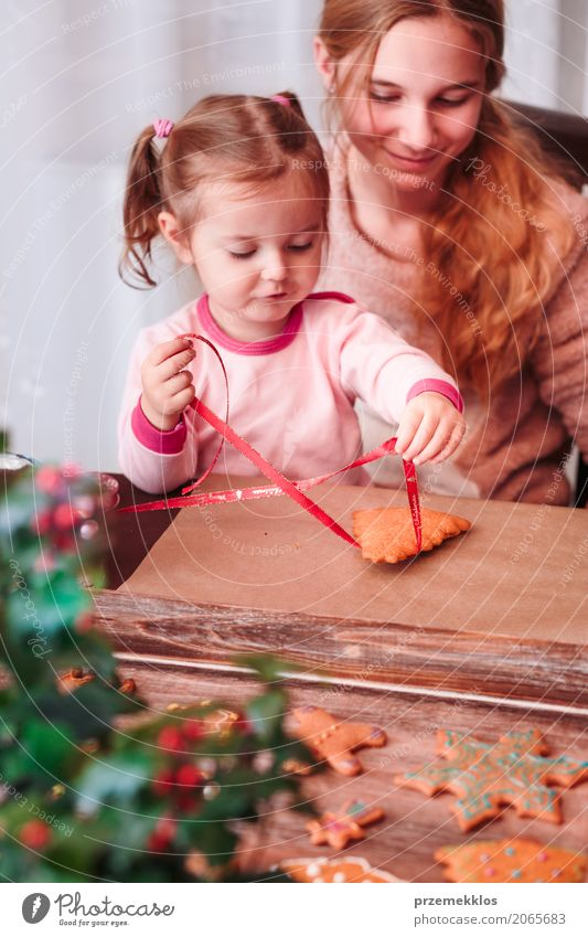 Girls tying baked Christmas gingerbread cookies with ribbon Human being Child Youth (Young adults) Lifestyle Family & Relations Feasts & Celebrations Decoration