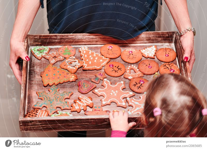 Little girl looking at tray filled with Christmas cookies Decoration Table Kitchen Feasts & Celebrations Child Craft (trade) Human being Woman Adults