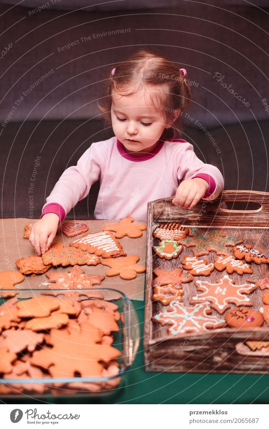 Little girl placing Christmas gingerbreads on wooden tray Human being Child Christmas & Advent Girl Lifestyle Feasts & Celebrations Decoration Table String