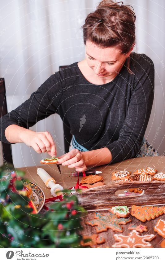 Woman decorating baked Christmas gingerbread with frosting Food Table Kitchen Feasts & Celebrations Christmas & Advent Human being Adults 1 30 - 45 years
