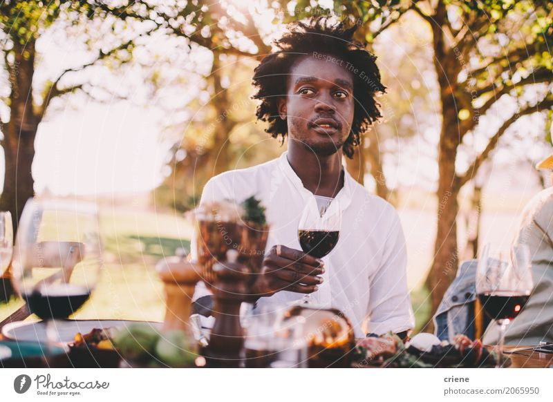 Afro American man enjoying wine at lunch party Human being Youth (Young adults) Man Summer Adults Warmth Eating Garden Food Masculine Park Smiling Table