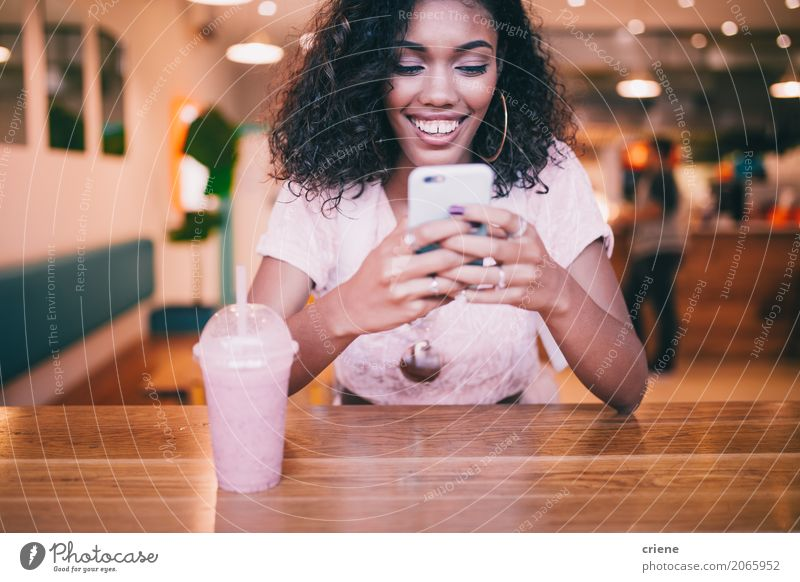 Smiling woman typing message on smartphone in Bar Beverage Drinking Lifestyle Joy Restaurant PDA Technology Internet Youth (Young adults) Email Afro Communicate