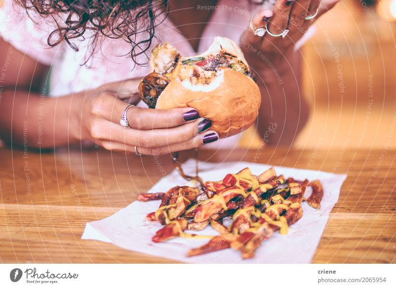 Close-up of woman eating fries and Hamburger Meat Bread Roll Herbs and spices Eating Diet Fast food Lifestyle Restaurant Woman Adults Afro Fat Delicious Joy