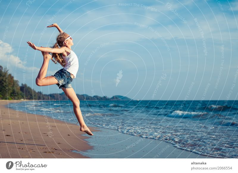 One teen girl jumping on the beach Human being Child Woman Nature Vacation & Travel Summer Sun Hand Ocean Relaxation Joy Beach Adults Lifestyle Emotions Sports