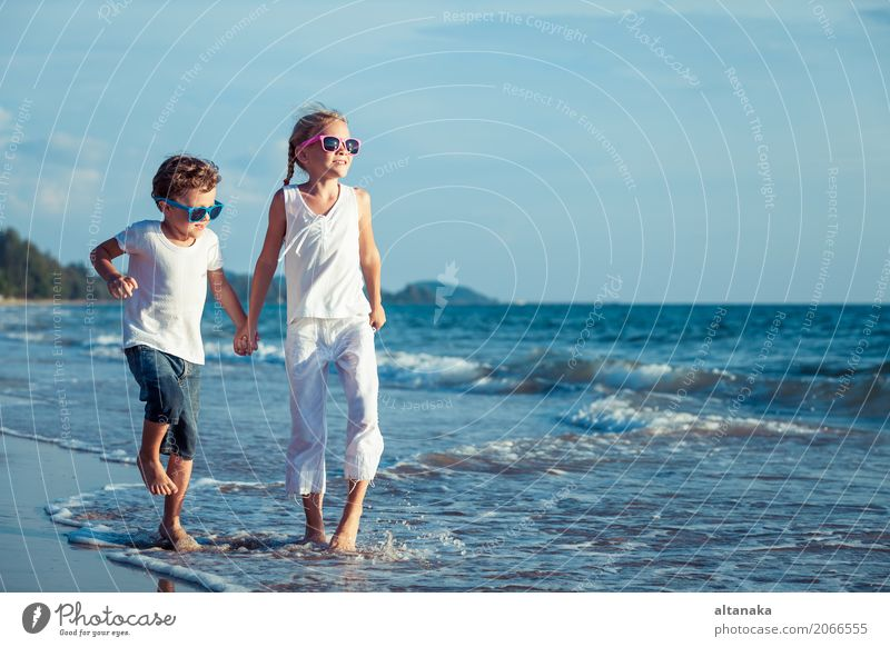 Happy children playing on the beach Human being Child Nature Vacation & Travel Summer Sun Hand Ocean Relaxation Joy Beach Lifestyle Emotions Sports