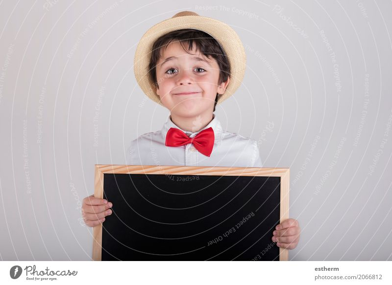 smiling child holding a blackboard Lifestyle Joy Child Blackboard Schoolchild Human being Masculine Toddler Boy (child) 1 3 - 8 years Infancy Tie Hat To hold on