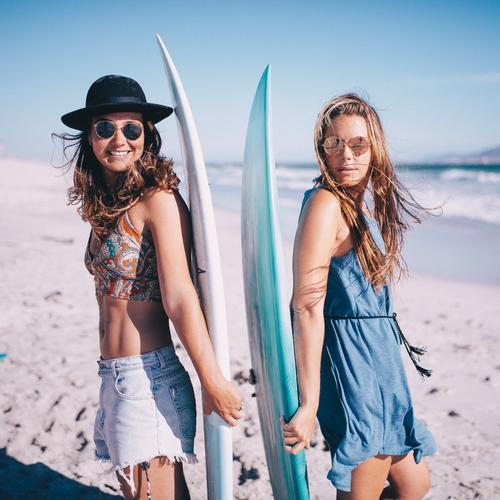 Portrait of two young woman with surfboards on beach Lifestyle Joy Leisure and hobbies Vacation & Travel Summer Sunbathing Beach Ocean Sports Human being