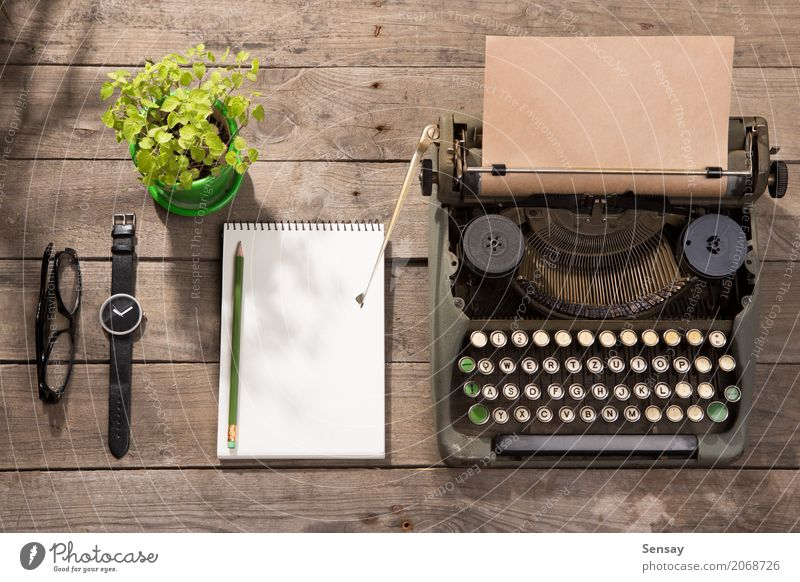 Vintage typewriter on the old wooden desk Coffee Tea Pot Desk Table Workplace Office Newspaper Magazine Book Plant Paper Wood Old Observe Write Retro Green