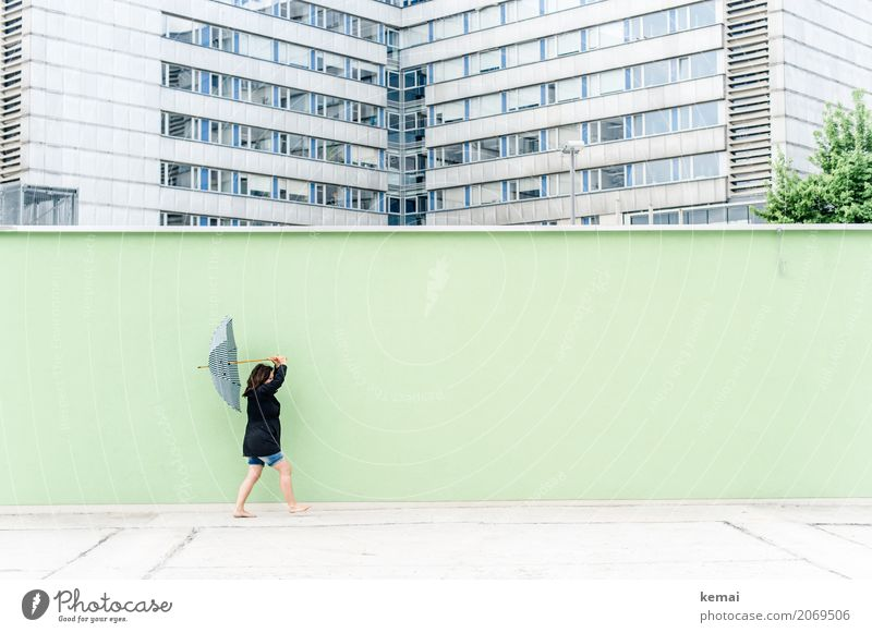 Woman with umbrella in front of a green wall, in the background skyscrapers Lifestyle Harmonious Leisure and hobbies Trip Freedom Human being Feminine Adults 1
