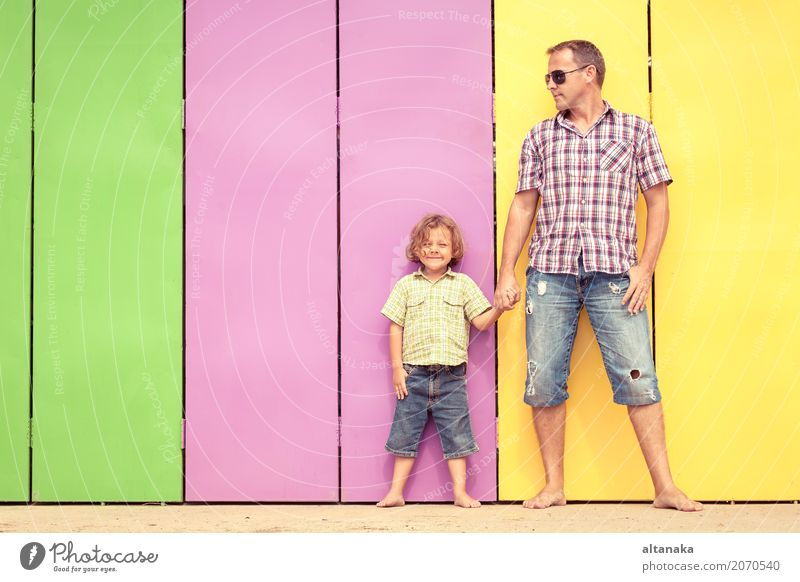 Father and son relaxing near the house at the day time. They standing near are the colorful wall. Concept of friendly family. Lifestyle Joy Happy Relaxation