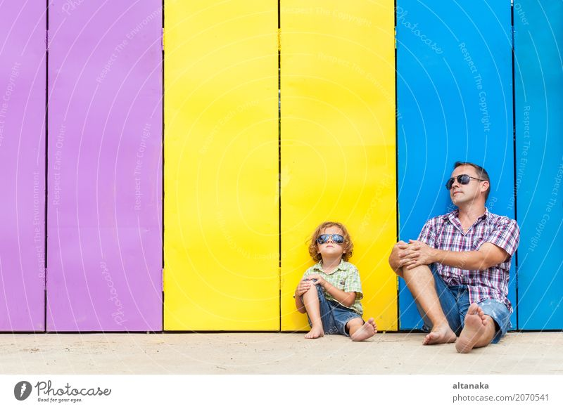 Father and son relaxing near the house at the day time. They sitting near are the colorful wall. Concept of friendly family. Lifestyle Joy Happy Relaxation