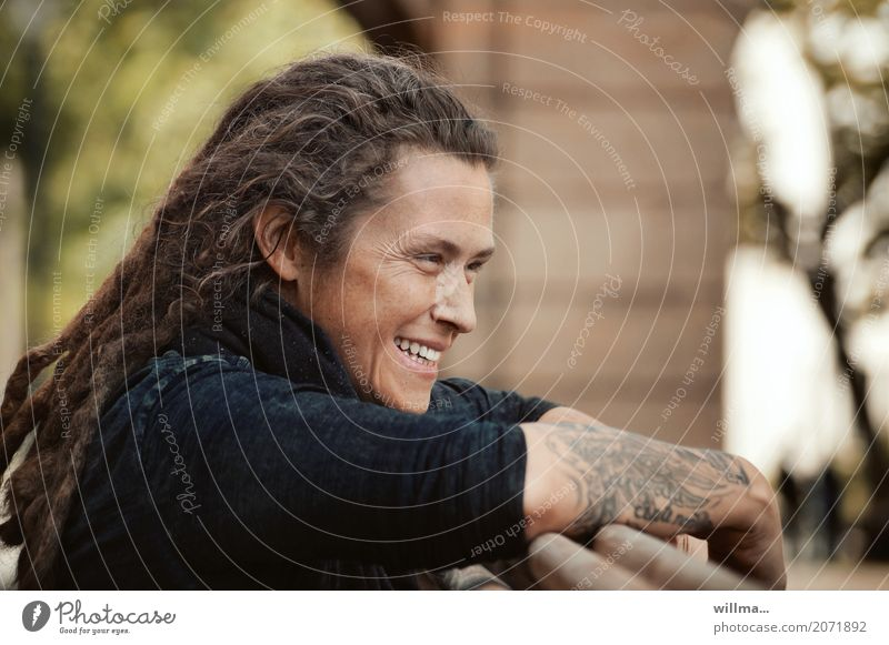 Tattooed young woman with dreadlocks smiles mischievously Young woman Youth (Young adults) rastas Laughter contented Easygoing Long-haired Dreadlocks Happiness
