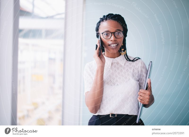African businesswoman in a conversation on the phone Woman Youth (Young adults) Young woman Adults To talk Feminine Business Work and employment Office Modern Success Stand Smiling Telephone Profession Career