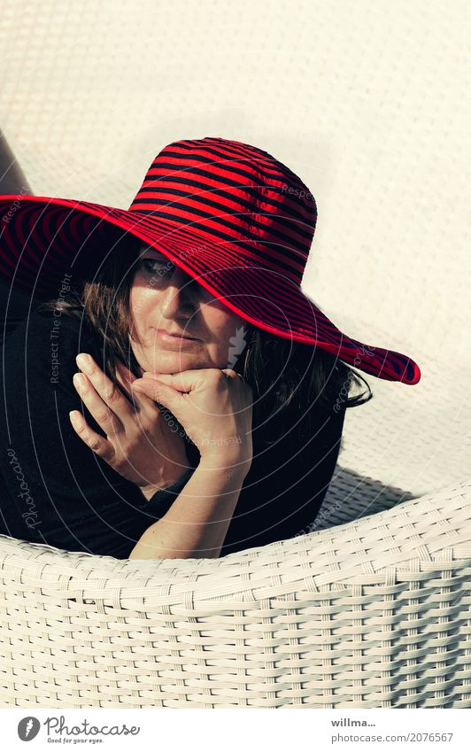 mature lady with red hat relaxes on white basket couch in the sun Lifestyle Elegant Harmonious Well-being Contentment Relaxation Summer Summer vacation