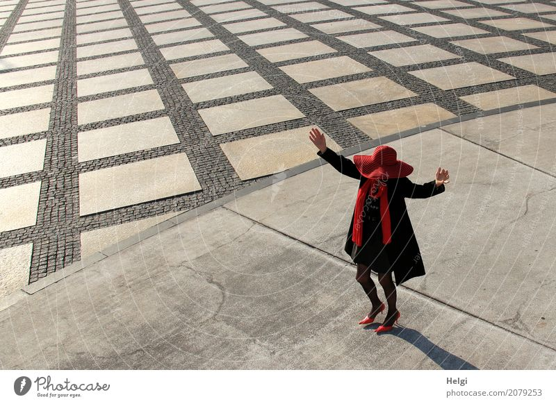 elegantly dressed lady with black coat, red hat, red scarf and red pumps is dancing on a large square with concrete and patterned floor Human being Feminine