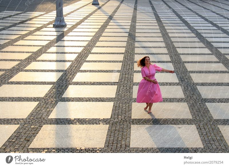 Woman with long brunette waving hair and pink dress dancing barefoot on a large paved square against the light Human being Feminine Adults 1 45 - 60 years Town
