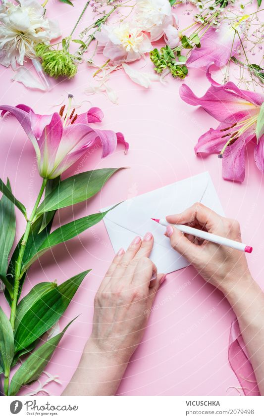 Female hands write greeting card on pink table with flowers Lifestyle Style Design Living or residing Decoration Table Feasts & Celebrations Valentine's Day