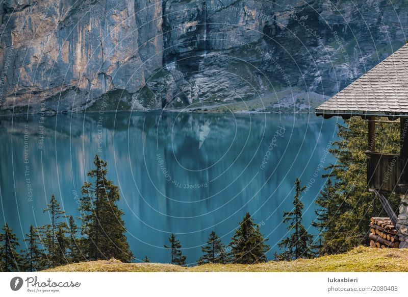 Mountain hut at Oeschinensee with intensive blue reflection Environment Nature Landscape Water Spring Summer Weather Beautiful weather Tree Grass Rock Lakeside