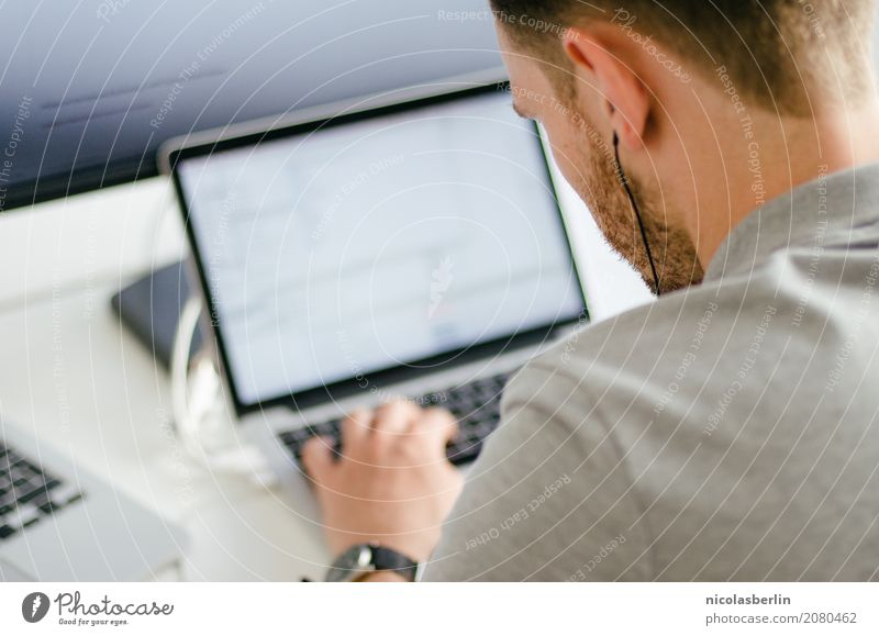 Young man works on a laptop in the start-up and listens to music through in-ear headphones Professional training Apprentice Internship Study