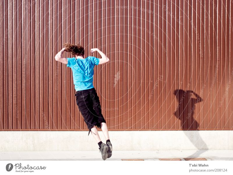 standing jump Joy Leisure and hobbies Sports Human being Masculine Young man Youth (Young adults) Arm Strong Jump Body tension Wall (building) Brown Flying