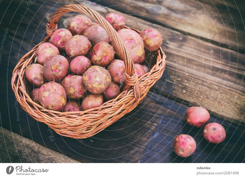 Raw potatoes Vegetable Nutrition Vegetarian diet Table Wood Fresh Natural Brown Red agriculture background Basket cooking Crops Edible food Harvest healthy