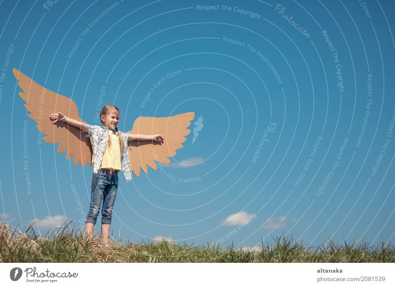 Little girl playing with cardboard toy wings in the park Human being Child Sky Nature Vacation & Travel Summer Sun Joy Lifestyle Sports Grass Small Playing