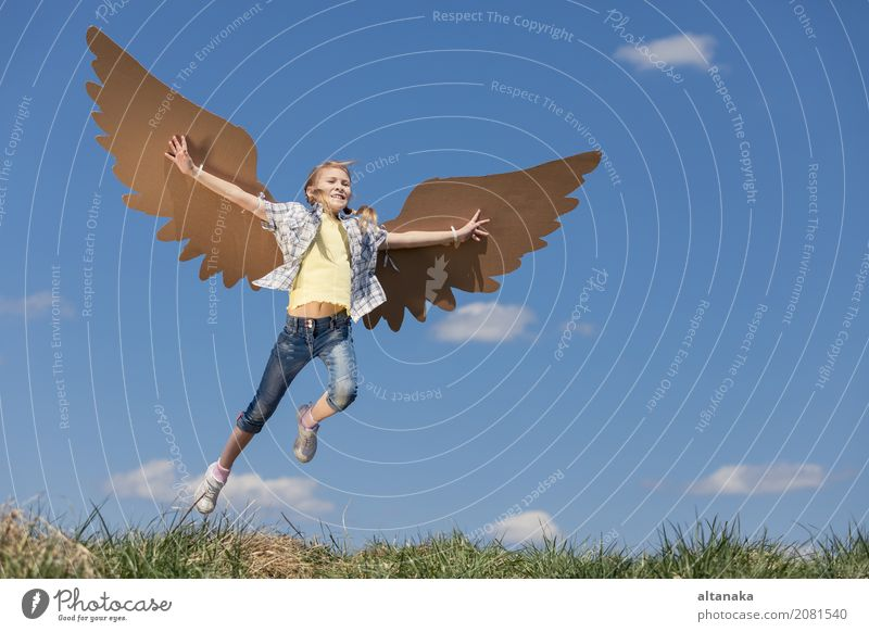 Little girl playing with cardboard toy wings in the park at the day time. Concept of happy game. Child having fun outdoors. Picture made on the background of blue sky.