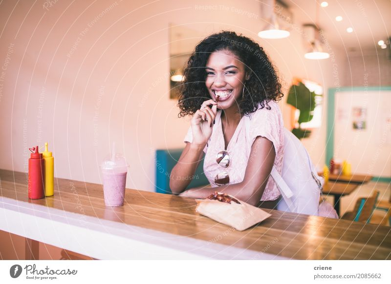 Young african woman eating potato fries in restaurant Food Eating Lunch Dinner Fast food Lifestyle Joy Leisure and hobbies Restaurant Human being Feminine