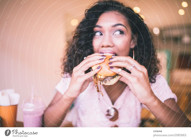 Woman taking bite of hamburger in restaurant Human being Youth (Young adults) Young woman Adults Eating Lifestyle Feminine Food Smiling To enjoy Restaurant Café