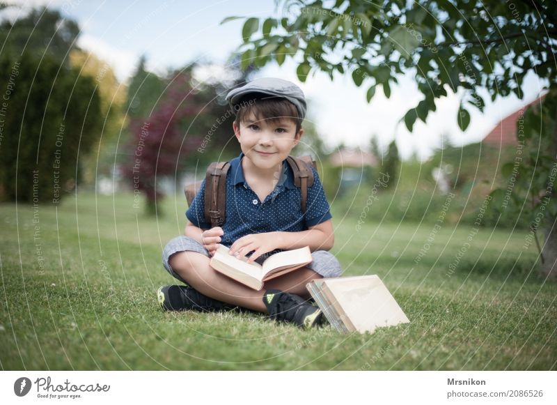enrolment Human being Child Boy (child) Infancy Life 1 3 - 8 years Smiling Study Sit Cap First day at school Book Ancient Satchel Meadow Garden Exterior shot