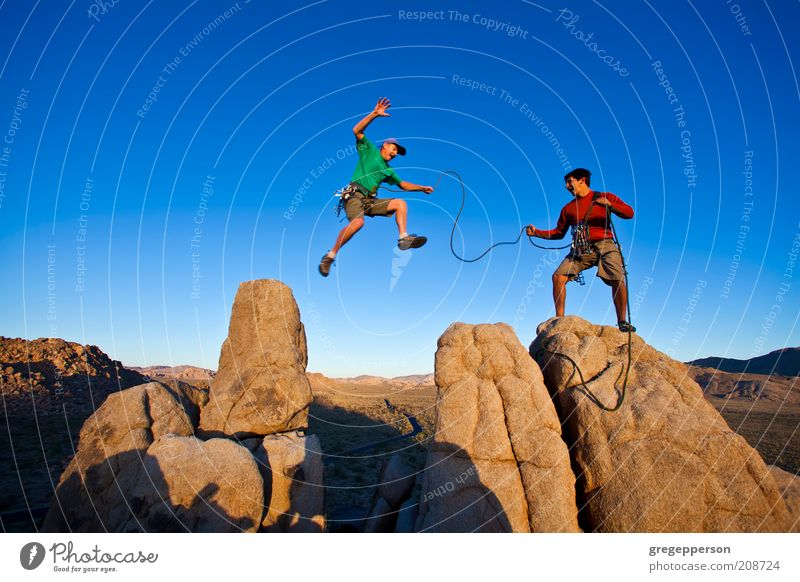 Team of climbers on the summit. Human being Adults Life Mountain Jump Sports Power Rock Flying Tall Masculine Adventure Dangerous Rope Success Climbing
