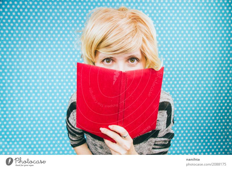 Young blonde woman covered by a book Human being Youth (Young adults) Blue Young woman Red 18 - 30 years Adults Yellow Lifestyle Feminine Hair and hairstyles