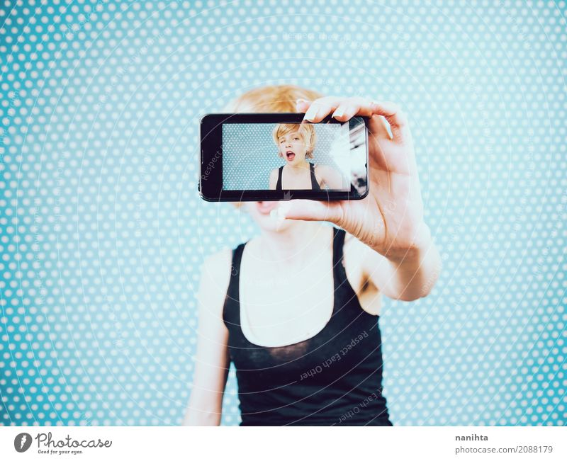 Young woman taking a self portrait with her mobile phone Human being Youth (Young adults) Blue White Hand 18 - 30 years Adults Life Lifestyle Feminine