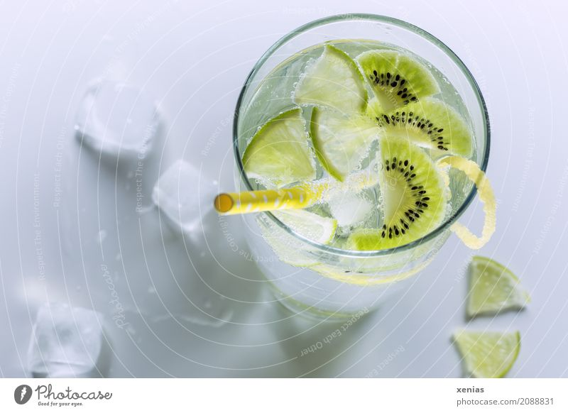 Refreshing cool soft drink with kiwi and lime in a glass with yellow straw Beverage Kiwifruit Slices of lime Lemon peel Limone Cold drink Drinking water