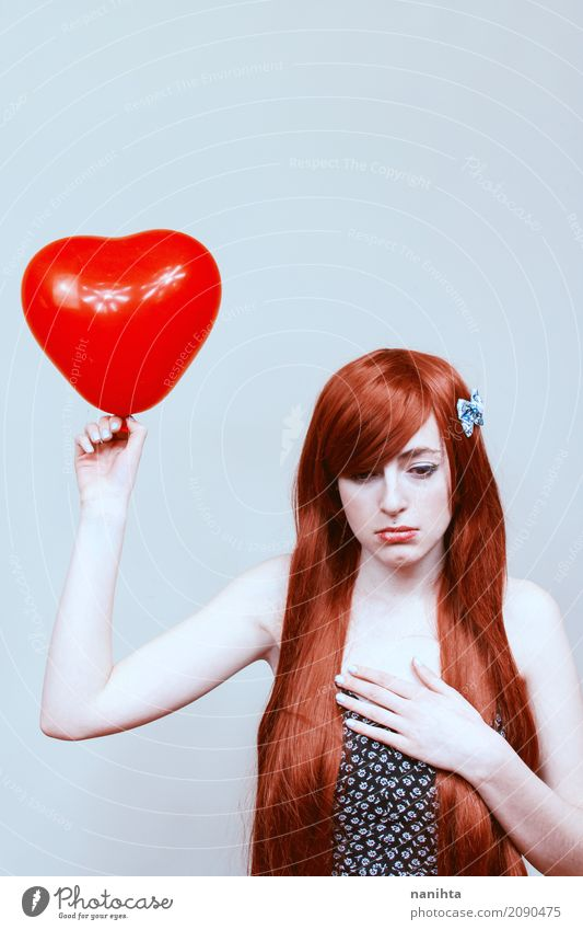 Young sad woman holding a heart shaped balloon Human being Youth (Young adults) Young woman White Red Loneliness 18 - 30 years Black Adults Sadness Love
