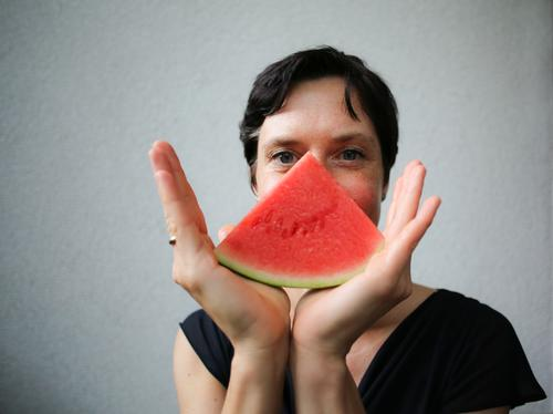 Woman with melon piece in front of her face Fruit Melon Nutrition Organic produce Vegetarian diet Finger food Lifestyle Style Joy Leisure and hobbies Adults