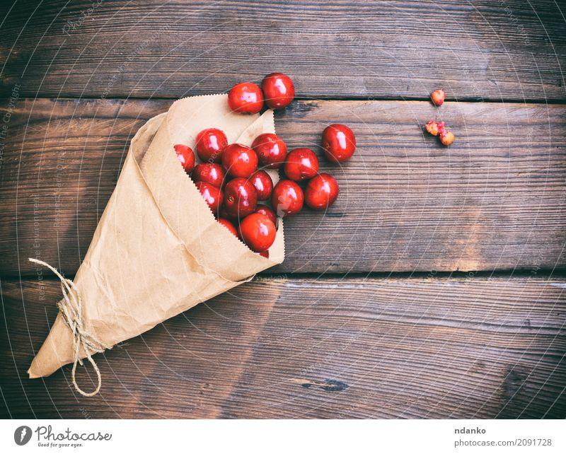 Ripe red cherry in a paper bag Fruit Dessert Vegetarian diet Paper Wood Diet Eating Fresh Retro Juicy Red background Berries Cherry food Harvest many Organic