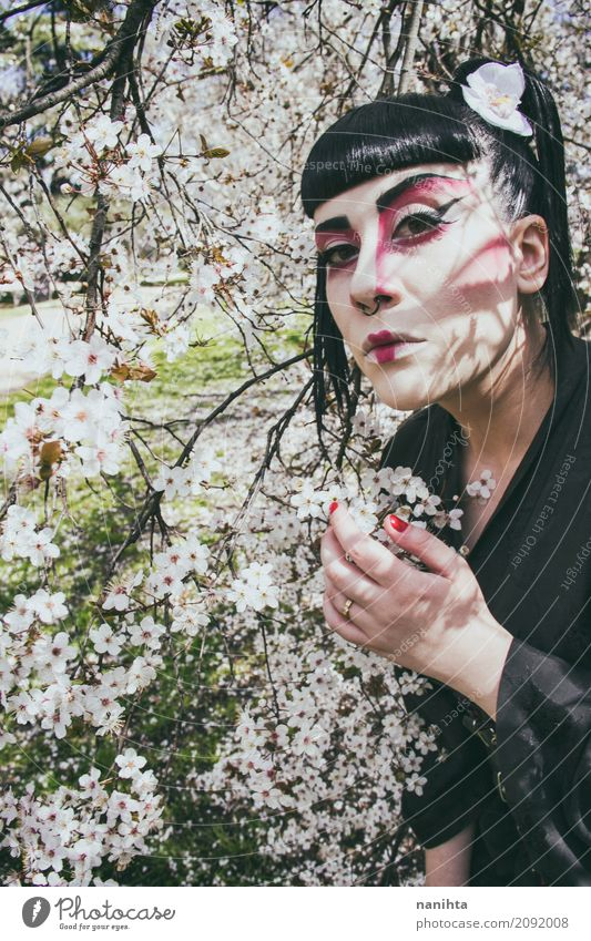 Young woman with a geisha costume pose with white flowers Human being Nature Youth (Young adults) Beautiful White Tree Flower 18 - 30 years Black Adults Spring