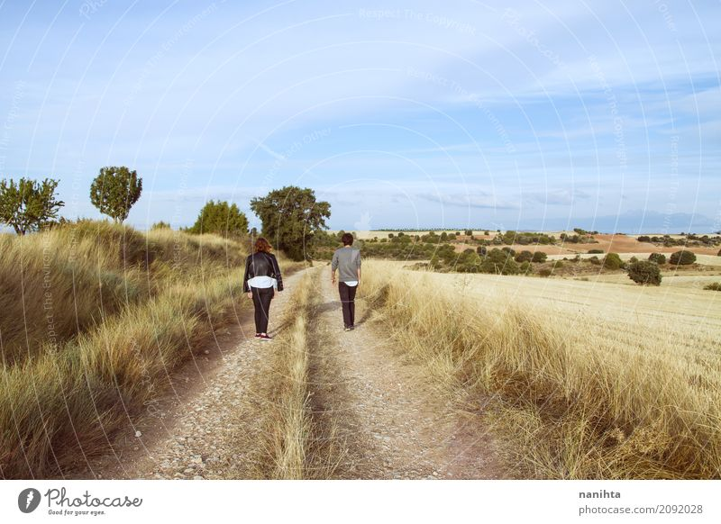 Young couple walking away on a rural path Human being Nature Vacation & Travel Youth (Young adults) Blue Young woman Young man Landscape Far-off places