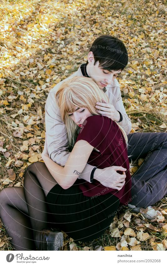 Young couple hugging in a park Human being Nature Youth (Young adults) Young woman Young man Relaxation Leaf 18 - 30 years Adults Environment Lifestyle Sadness