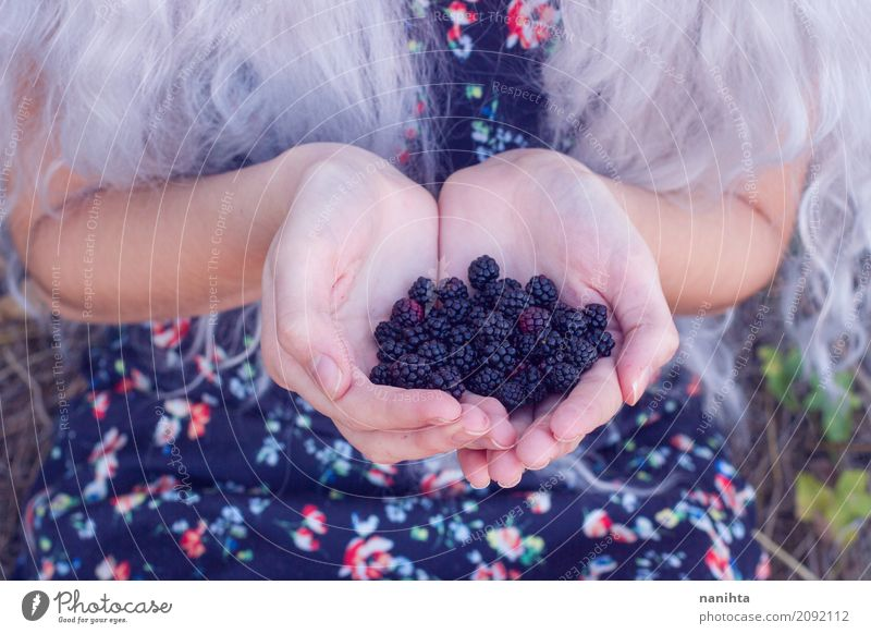 Woman holding a buntch of blackberries Human being Nature Youth (Young adults) Blue Young woman Hand 18 - 30 years Black Adults Life Lifestyle Healthy Natural