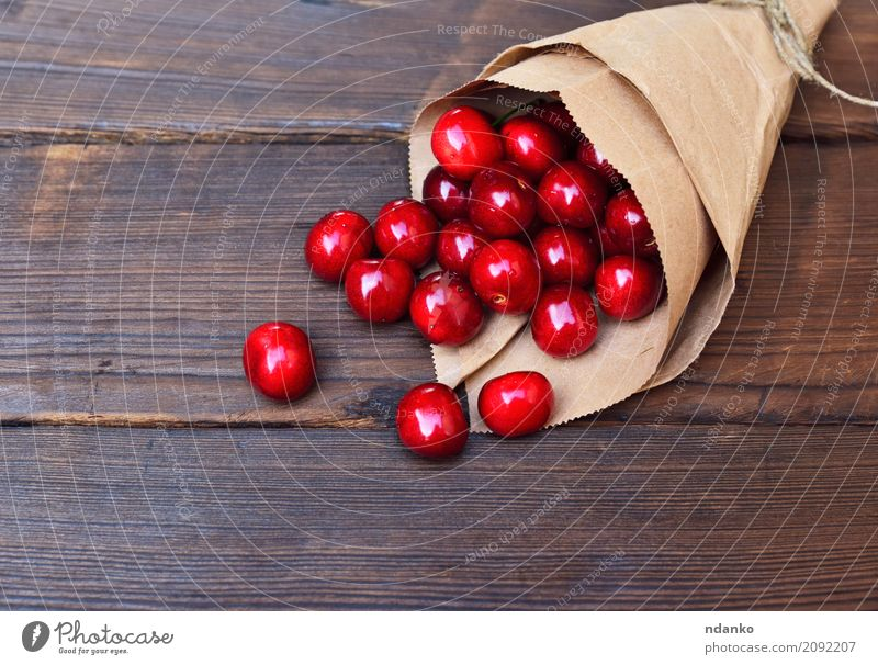 Red ripe cherry in a paper bag Fruit Dessert Eating Vegetarian diet Juice Summer Table Nature Paper Wood Fresh Natural Above Retro Juicy background Berries