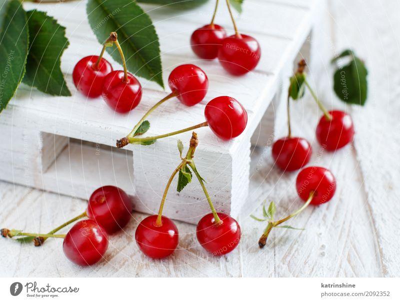 Fresh sour cherries on a white wooden table Summer Green Red Leaf Dark Brown Wild Fruit Fresh Table Delicious Berries Bowl Vegetarian diet Diet Vitamin