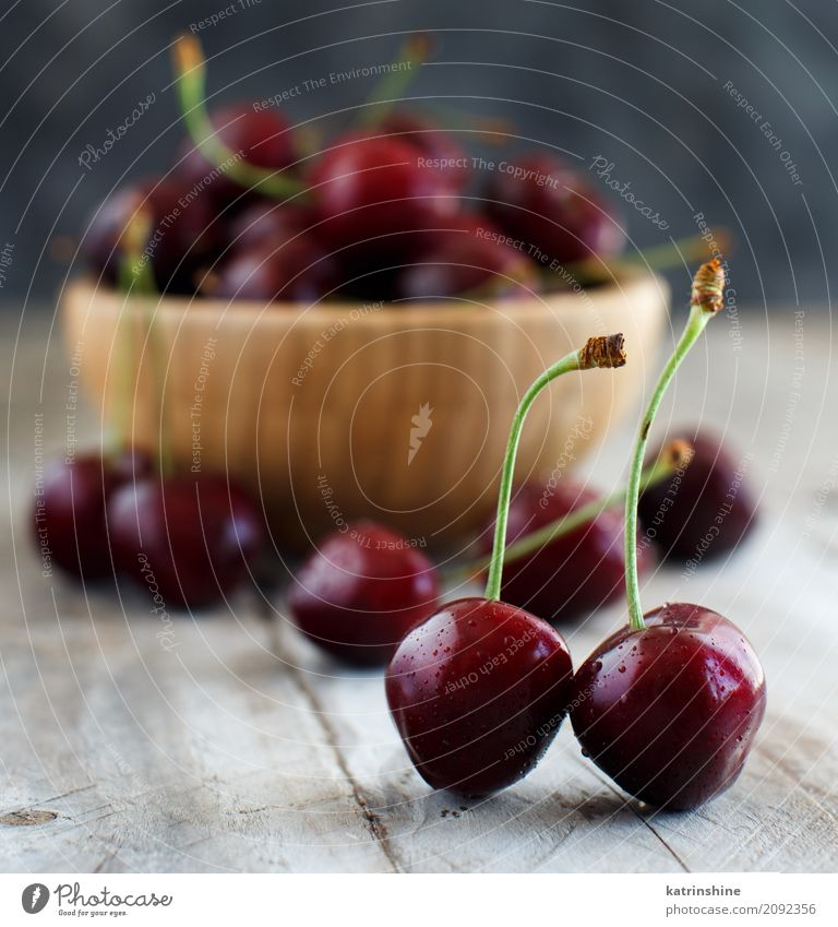 Red cherries in a bowl on a old wooden background Fruit Dessert Nutrition Vegetarian diet Diet Bowl Summer Table Group Dark Fresh Bright Delicious Juicy Berries